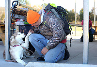 NWA Democrat-Gazette/DAVID GOTTSCHALK  Clarke Mitchell kneels down to pet his dog Alice Friday, February 24, 2017, next to his wagon filled with wood building materials and hand made walking sticks on the covered picnic area at 7 Hills Homeless Center in Fayetteville. Mitchell is one of the skilled laborers that hopes to work at the Independent Workshop, Homeless Workkshop, that is now in the planning stages.