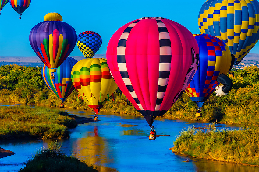 Hot air balloons flying low over the Rio Grande River just after sunrise, Albuquerque International Balloon Fiesta, Albuquerque, New Mexico USA.