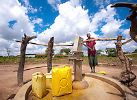 ALEBTONG DISTRICT: OMINO VILLAGE:  Bethmens, 62, gathers water at new borehole well in May of 2012. International Lifeline Fund is the construction partner for Water to Thrive and employs a staff of construction workers, drilling engineers and sanitation trainers, all Ugandan professionals, to implement and drill deep or shallow boreholes depending on the site and geological requirements. They also conduct extensive sanitation training for villagers, teaching safe hygiene and hand washing practices, safe water storage and cooking methods, that are a cornerstone of sustainable development and disease control.