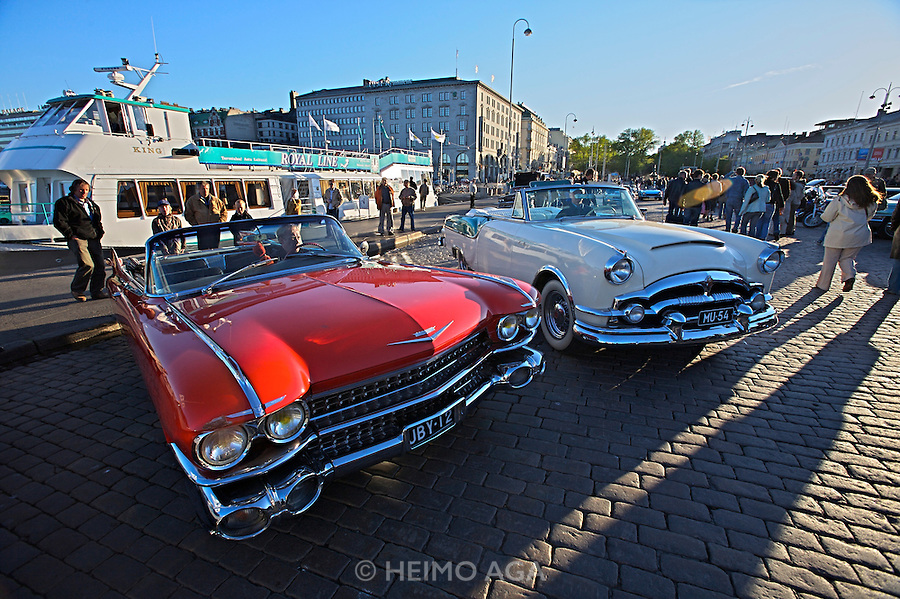 During summer from June to Septemper, every first Friday of the month is Vintage Car Cruising Night. Hundreds of classic American cars cruise around downtown Helsinki and meet at special places to have a good time, here at Kauppatori (Market Square). 1959 Cadillac DeVille convertible (l.).