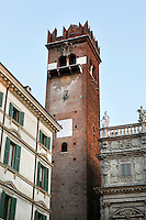 Low angle view of Gardello Tower and Palazzo Maffei, 15th-17th centuries (right), Piazza delle Erbe, Verona, Italy. The Gardello Tower was built in 1370 in brick by Cansignorio della Scala. The baroque Palazzo Maffei, was built in 1668 by Rolando Maffei. From the balustrade the Greek gods are overlooking the market life of the square. Picture by Manuel Cohen.
