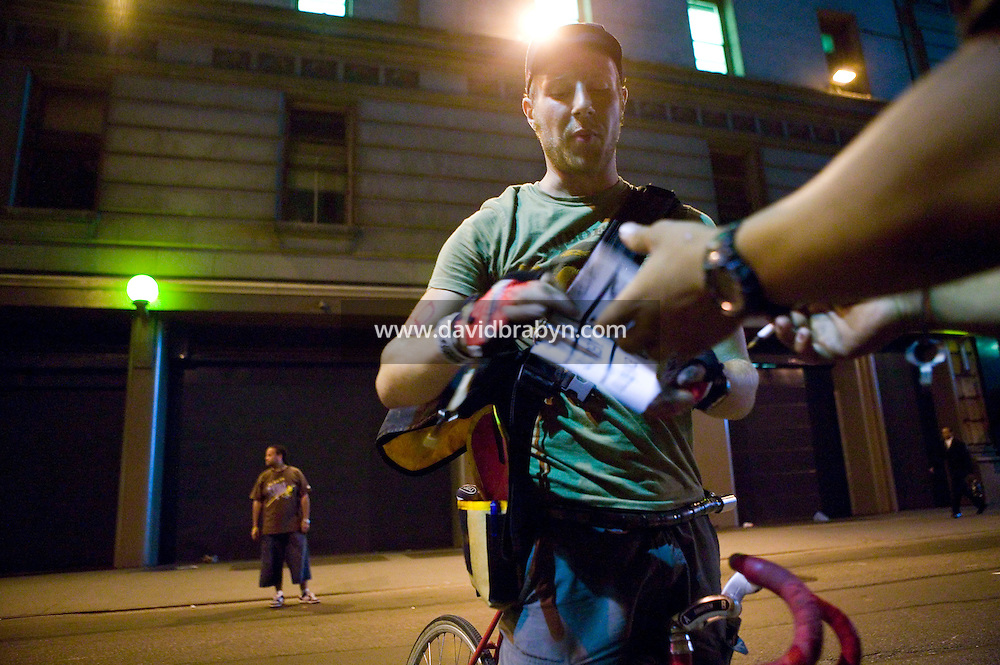 3 July 2005 - New York City, NY, USA - A rider gets his manifest stamped by &quot;Junjun&quot; (R, partly hidden) at an alleycat checkpoint on 43rd street in New York City, USA, July 3rd 2005, as Richard (L, background) waits for more riders to arrive. Alleycats are urban cycle races held informally - without notification of the authorities - on open roads and in real traffic, to simulate the messenger's working conditions. Photo Credit: David Brabyn<br />