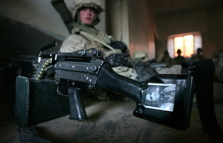 A picture of a girlfriend adorns the butt-stock of a SAW machine-gun carried by a Marine from Lima Co. 3rd Battalion 6th Marines search for insurgents during the sixth day of Operation Steel Curtain, an operation to clear Husaybah and Karabilah (two cities on the Iraq-Syrian border) of insurgents on Thurs. 10, 2005.
