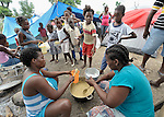 Women providing food to children living in a camp for homeless families in Jacmel. The families lost their homes--and some of their members--to the January 12 earthquake.