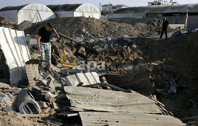 Palestinians inspect the damage to a smuggling tunnel after it was targeted in an Israeli air strike in Rafah, in the southern Gaza Strip August 19, 2011. Israeli aircraft struck Hamas security installations in Gaza on Friday, killing at least one Palestinian, in further retaliation for attacks along the Egyptian border in which eight Israelis died. Photo by Abed Rahim Khatib
