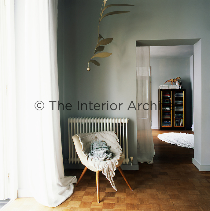 A retro armchair is set in the corner of the living room. The room has soft grey walls and parquet flooring. An open doorway gives a view through to the room beyond