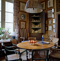 A collection of cane-backed chairs surround a circular table in this elegant but small breakfast room