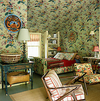 A combination of floral fabrics accessorised with colourful Tahitian masks assaults the senses in this master bedroom under the eaves