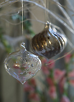 Detail of a pair of glass baubles hanging from a silver bough