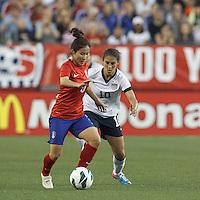 Korea Republic midfielder Lee Sejin (5) dribbles as USWNT midfielder Carli Lloyd (10) defends. In an international friendly, the U.S. Women's National Team (USWNT) (white/blue) defeated Korea Republic (South Korea) (red/blue), 4-1, at Gillette Stadium on June 15, 2013.