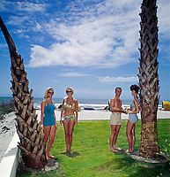 Young women in bikinis standing on the Thunderbird Motel lawn overlooking the ocean.