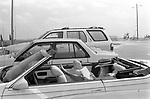 Woman reading a book in open top sports car Lake Worth USA 1999
