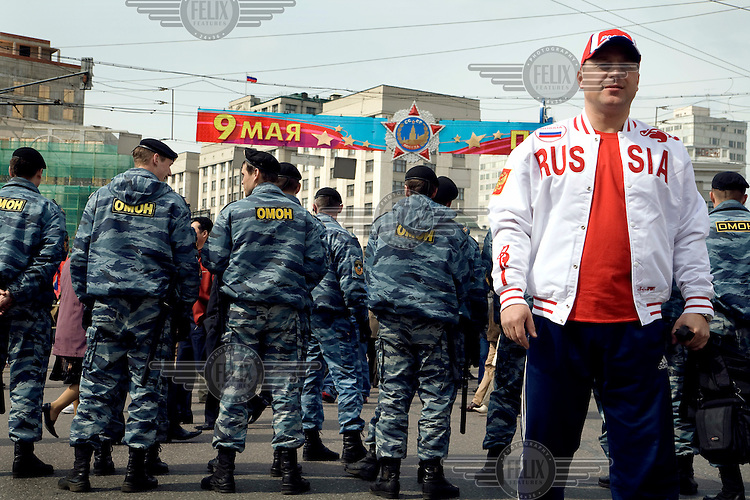 "A man wearing a ""Russia"" jacket stands in front of riot police guarding a demonstration by Communist supporters on Labour Day."