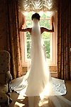 Bride looks out window prior to her ceremony.  View of her dress frm behind.