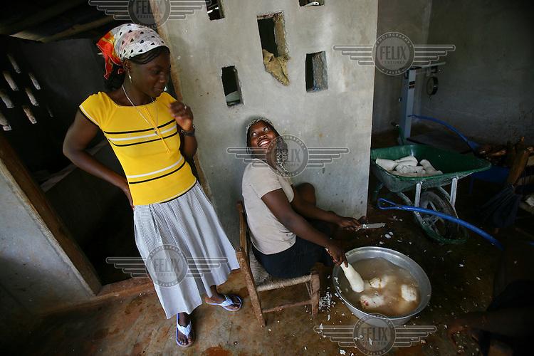 Jane Phillip laughs with Nana Caprena as she peels manioc (cassava) at the Flour Mill in Cap Rouge.