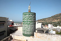 Circular minaret of a mosque in Moulay Idriss, dated 1939, decorated with green and white tiles with Koranic inscriptions, Meknes-Tafilalet, Northern Morocco. This is the only circular minaret in Morocco. The town sits atop 2 hills on Mount Zerhoun and was founded by Moulay Idriss I, who arrived in 789 AD and ruled until 791, bringing Islam to Morocco and founding the Idrisid Dynasty. It is an important pilgrimage site for muslims. Picture by Manuel Cohen