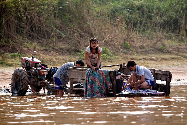 Laos villagers wash clothes in the Mekong River opposite of Sop Ruak, Thailand. A newly constructed casino displaced one of the Laos villages. Photo taken on Thursday, December 10, 2009. Kevin German / Luceo Images