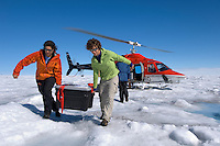 Scientists unloading research equipment from a helicopter on the Greenland ice cap.