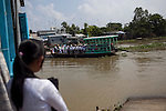 """A school girl watches as her classmates cross the Hau Giang River, a tributary of the Mekong River, in Long Xuyen, the capital of An Giang Province, Vietnam. She was late from school and missed they ferry. When the Mekong River reaches Vietnam it splits into two smaller riveres. The """"Tien Giang"""", which means """"upper river"""" and the """"Hau Giang"""", which means """"lower river"""". Photo taken on Monday, December 8, 2009. Kevin German / Luceo Images"""