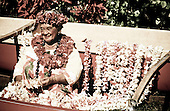 Aunty Maddie Kalihi, a Kodak hula show dancer, sits adorned with lei next to an outrigger canoe