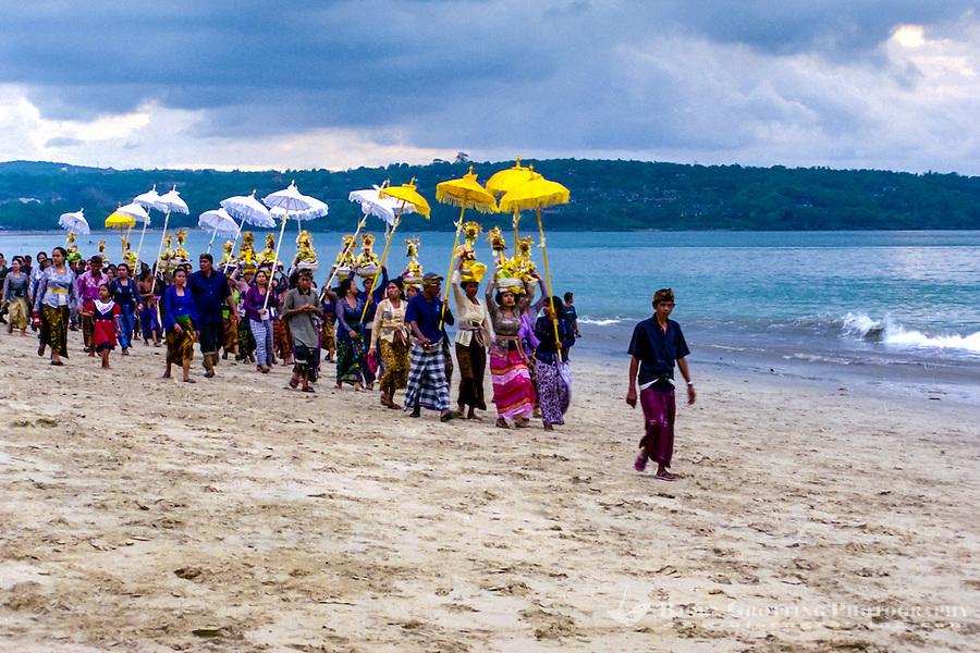 Bali, Badung, Jimbaran. A hindu ceremony held on the beach just before sunset.