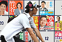 June 25, 2010 - Tokyo, Japan - A man rides a bicycle in front of a billboard of candidates posters during the Upper House election in Tokyo, Japan, on June 25, 2010. A July 2-4 survey by the Sankei newspaper showed that the DPJ may win between 48 and 55 of the 121 seats up for grabs in the 242-member upper house.