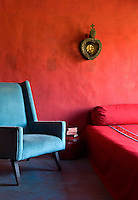The house has a colour scheme based on natural materials yet there are areas of vibrant colour such as the wall of this bedroom, where an intense red pigment has been used