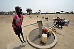 A girl pumps water from a well provided by the Catholic Church in Leu, a village in the contested Abyei region along the border between Sudan and South Sudan. The village was looted and burned in 2011 when soldiers and militias from the northern Republic of Sudan swept through the area, chasing out more than 100,000 Dinka Ngok residents. A few thousand families have returned since northern combatants withdrew in 2012, yet their life is precarious. In Leu, the church rehabilitated a clinic and drilled this well. For political and logistical reasons, the Catholic Church is one of the few organizations willing to openly accompany the people of Abyei during these uncertain times.