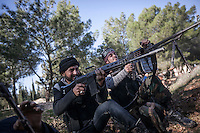 Syrian rebel fighters aim their weapons toward government forces during heavy clashes at Madrasat Al-Mushaat, one militar academy besieged by rebels at the north of Aleppo, Syria.
