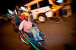 A man in a wheelchair is raced down Oxford Street in Accra, Ghana as a boy on one skate clings to a car going in the opposite direction as Ghanaians celebrate their World Cup defeat of the USA on 26 June 2010.