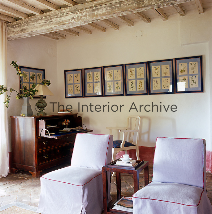 In the sitting room the dusky-pink of the skirting and the lavender in the picture frames is echoed in the upholstery of the pair of chairs