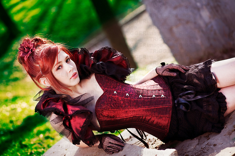 Redhead dressed in Victorian style sitting on stairs
