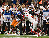 Mike Gillislee of Florida runs the ball away from James Burgess of Louisville during 79th Sugar Bowl game at Mercedes-Benz Superdome in New Orleans, Louisiana on January 2nd, 2013.   Louisville Cardinals defeated Florida Gators, 33-23.