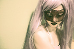 A young woman with long blonde hair wearing a party mask looking down sadly