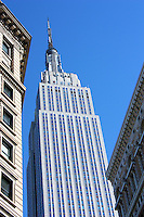 The Empire State building soars skyward from between two other buildings in NYC