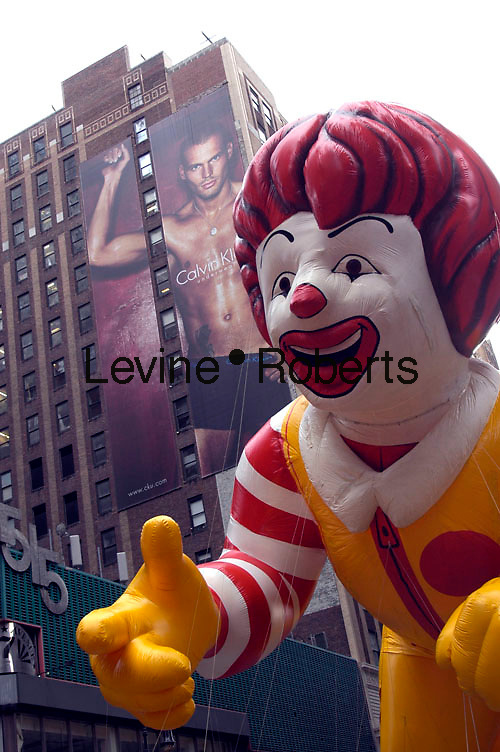 Volunteer Macy's employees maneuver the Ronald McDonald balloon past a Calvin Klein billboard at the 79th Macy's Thanksgiving Day Parade. The festive parade was marred by an accident where a balloon shaped like an M&M snagged a light pole causing a piece of it to fall into the crowds of spectators in Times Sqaure injuring at least two persons. (© Richard B. Levine)