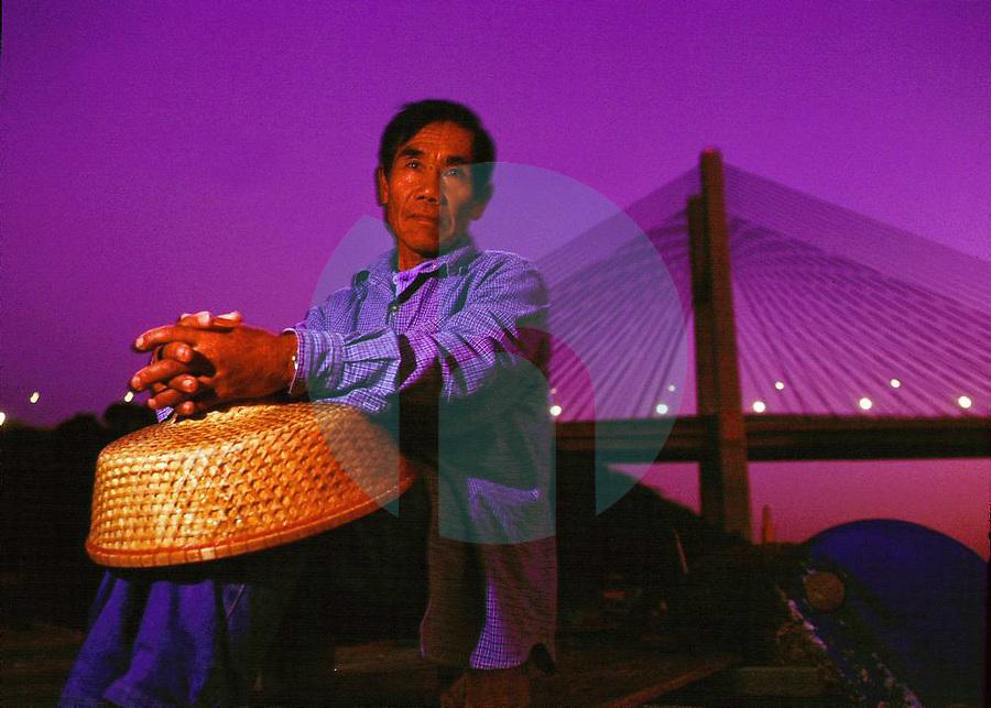 March 3rd 2000- HONG KONG ÐA Hong Kong fisherman sits in his boat, as the Tsing Ma bridge looms in the background.  The Tsing Ma bridge links Hong Kong to itÕs international airport, which is on Lantau Island.  Photo by Daniel J. Groshong/Tayo Photo Group