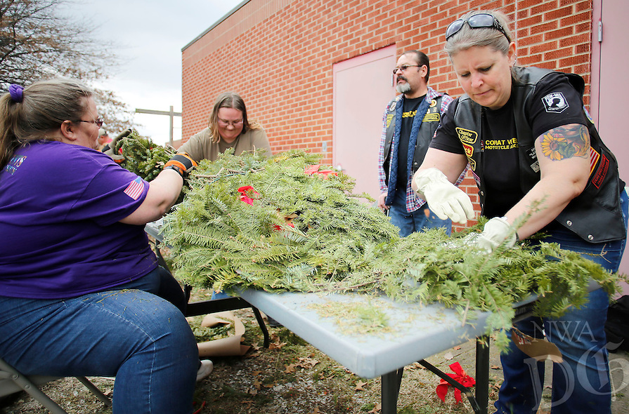 NWA Democrat-Gazette/DAVID GOTTSCHALK  Myra Zuber (from left), Janna Schlais, Richard Zuber and Cindy Whiteaker (cq), all volunteers with with Bo's Blessings from Bentonville, break down wreaths Friday, February 19, 2016, as she participates in the fourth annual Wreath Recycling Event at the National Guard Armory in Fayetteville. More than 9,000 wreaths collected from the Fayetteville National Cemetery are being broken down for recycling purposes and a bonfire memorial service. All money raised from the event will be donated to the Regional National Cemetery Improvement Corporation for land purchases for the cemetery. Bo's Blessings is a non-profit organization honoring Bo Swearingen, an Army veteran, who died in April of 2010.