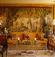 A pair of Venetian giltwood mirror and candle sconces on a large Aubusson Louis XV tapestry which dominates one wall of the drawing room
