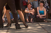 Katharina Wiest, center, and Laudia Manthey, right, of Germany, watch tango performers in the Plaza Dorrego in Buenos Aires.<br />