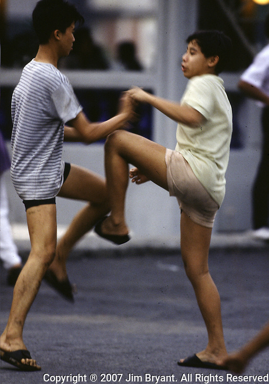 In a country noted for the sport of kick boxing, two boys practice their fighting skills in a street in Bangkok, Thailand. (Jim Bryant Photo).....