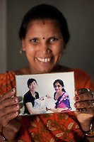 "Shardaben holds up a photograph of her first surrogacy job..Shardaben Kantiben, 31; Husband is Kantibhai Motibhai (37).3 children --- 2 girls -  Usha(15) and Lakshmi (18, in pink); 1 boy, Chintan (17).- Education costs for all three come to Rs. 15,000 per year.- Shardaben was a two-time surrogate. First time she gave birth to twin girls for a Taiwanese couple and the second time a boy for an Indian couple from America (photo on TV set because she's proud that it was a boy).- The second time she became emotional and they got a gold ring of Rs. 1,500 made for the boy, which they presented to the biological parents. They are not in touch with either couple..- From the two surrogacies, they earned a little over 700,000rupees..-200,000rupees will be given as dowry for Lakshmi's wedding..- They leased agricultural land (Rs. 2 lakhs for five years) which earns them Rs. 60,000-70,000 a year; they bought two buffaloes worth Rs. 60,000 and make almost 6000-7000 per month selling milk; they bought a motorbike for Rs. 25,000; they put some money into house repairs and the construction of toilets, and opened a fixed deposit in Shardaben's name for Rs. 1.5 lakh and one in the name of their son, Chintan, for Rs. 25,000..Quotes..""Everyone says they'll keep in touch and take down addresses and phone numbers but nobody looks back. And I guess it works well. Our main interest was in the money. Their main interest is in the baby."" - KantiBhai.""Their rules apply at the surrogate house. It does curtail the freedom. When I used to go, everybody would just be lying. They count the days when they can go back."" - Kantibhai.""Ours is natural birth but surrogacy is a man-made pregnancy. There's a lot of risk. She must have taken at least 300 injections."" - Kantibhai of his wife...The Akanksha Infertility Clinic is known internationally for its surrogacy program and currently has over a hundred surrogate mothers pregnant in their environmentally controlled surrogate houses. .Photo by Suzanne Lee"