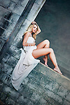 Young woman with blonde hair wearing a long white dress and pearl necklace sitting on a wall alone
