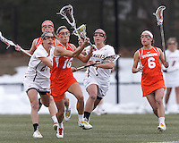 Syracuse University defender Linley Block (16) on the attack as Boston College midfielder Caroline Margolis (21) and Boston College midfielder Carly Weilminster (7) close.  Syracuse University (orange) defeated Boston College (white), 17-12, on the Newton Campus Lacrosse Field at Boston College, on March 27, 2013.