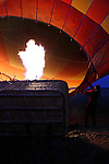 Africa, Kenya, Masai Mara. Preparing hot air balloon for flight as flame fills balloon.