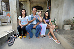 Martin Terrado sits with his daughters, Susana (left) 25, Janice 20, and Sunshine 16, in front of their home in Pangasinan in the Philippines. They are holding a photo of Martin's wife, Virginia, who went to Hong Kong in December 2007 to work as a domestic servant to help the family survive. She was placed with a family which beat her and called her names, and she finally took refuge in the Bethune House Migrant Women's Shelter.
