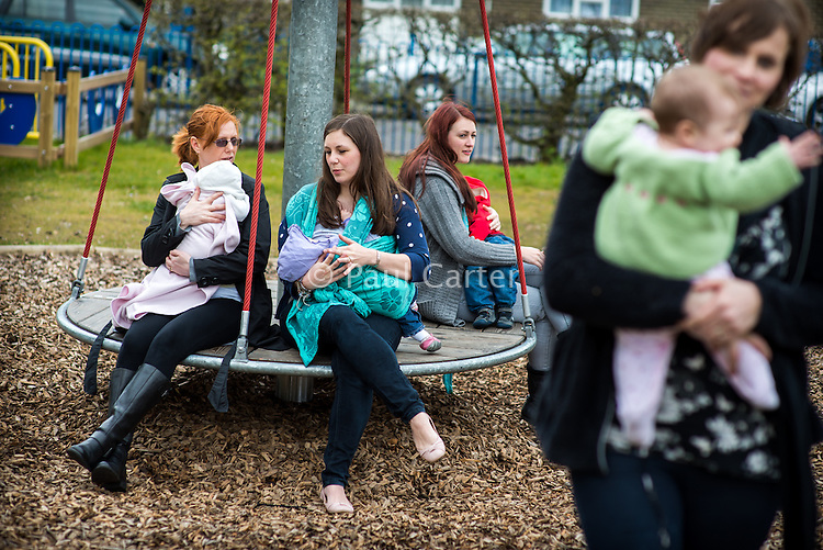 A group of women sit talking and breastfeeding their babies on a round-about in a children's playground. <br /> <br /> Image from the &quot;We Do It In Public&quot; documentary photography project collection: <br />  www.breastfeedinginpublic.co.uk<br /> <br /> Dorset, England, UK<br /> 17/04/2013