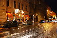 Prague street with tram lines at night: cars, cafe, lights.