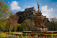 The Edinburgh Castle seen from the Princes Street Gardens, with the Ross Fountain, Edinburgh, Scotland. On a spring sunny day, the Princes Street Gardens are a very popular spot for locals and tourists alike. The Edinburgh Castle stands on top of the Castle Rock, the remnants of a volcano, and dominates the city skyline.