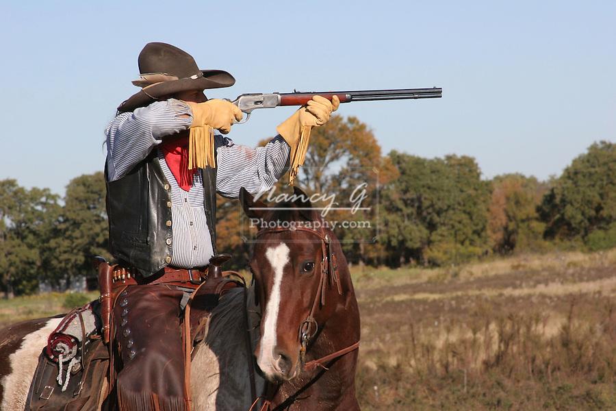 A cowboy on horseback taking aim